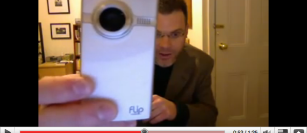 Screen shot of Bill in a YouTube video holding the Flip Video camera as he explains to the viewer the purpose of the class.